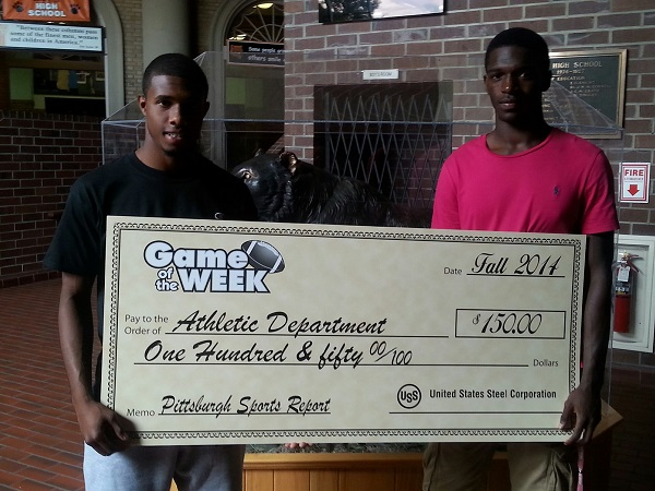 Raymone Clifford and Aaron Mathews display US Steel's donation to Clairton High School's athletic department